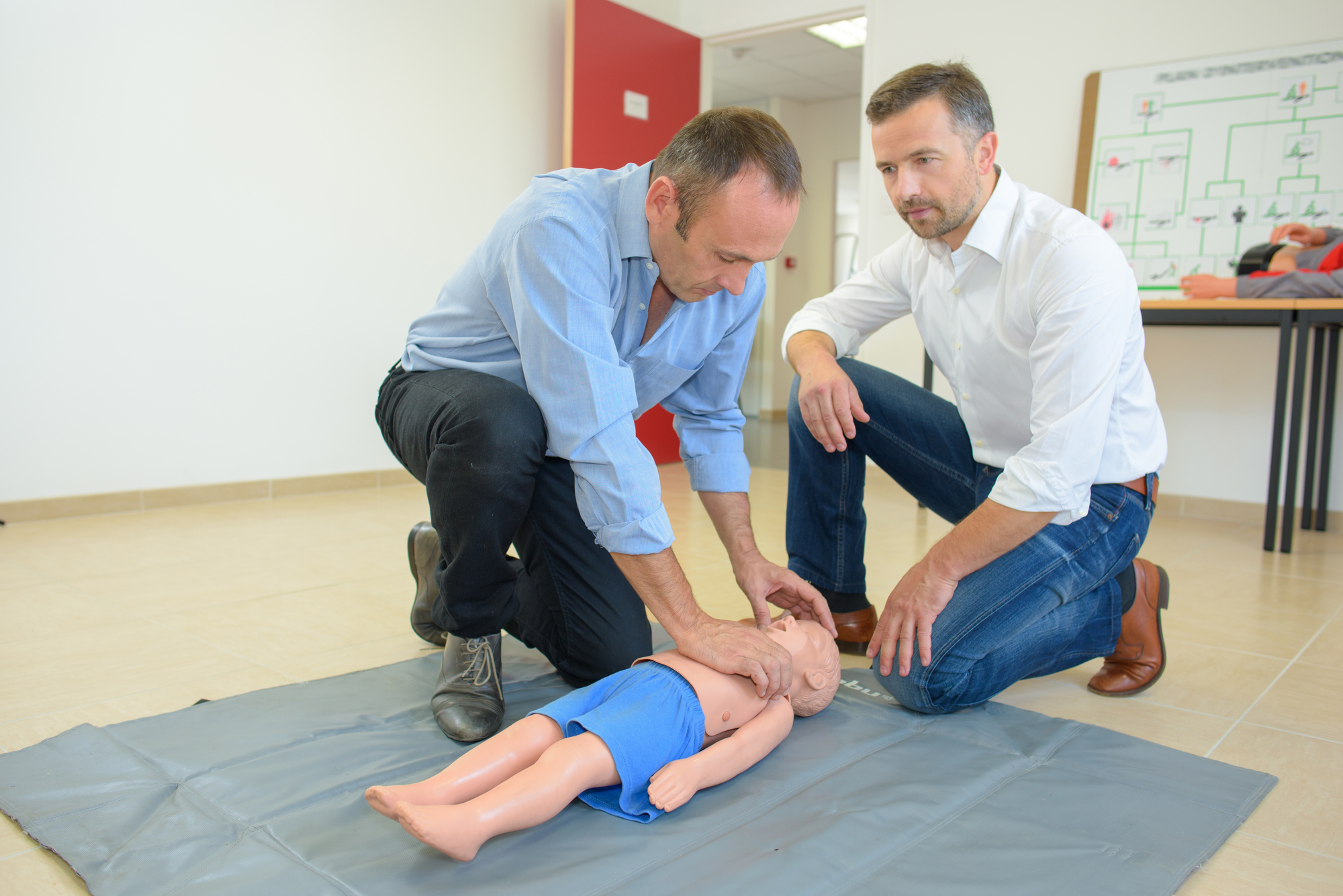 Men performing first aid on a child sized dummy